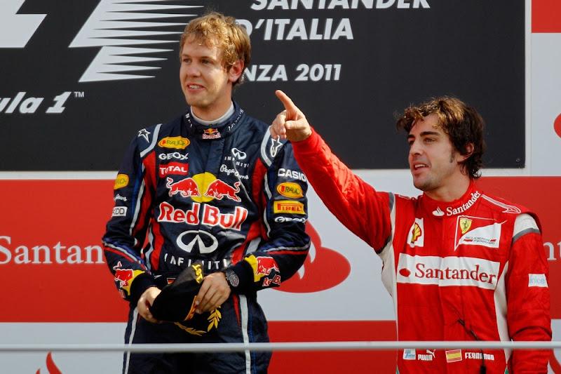 Фернандо Алонсо указывает пальцем куда-то Себастьяну Феттелю на подиуме Монцы на Гран-при Италии 2011