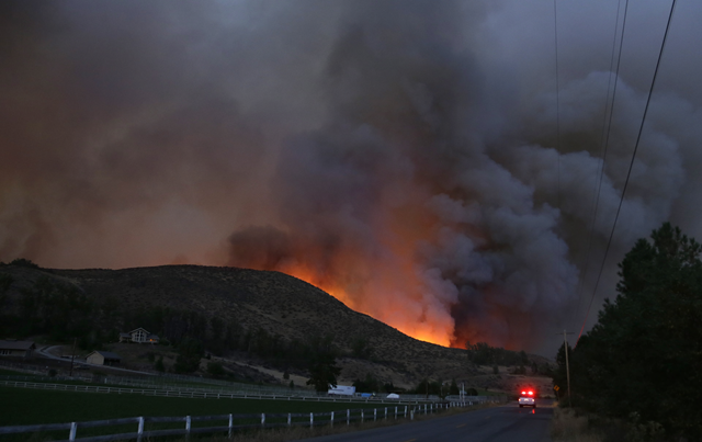 An emergency vehicle drives down Twisp River Road as a wildfire burns over the hillside, 20 August 2015. Photo: Ted S Warren / AP