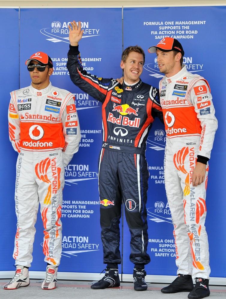 ебастьян Феттель смотрит на Дженсона Баттона и Льюис Хэмилтон рядом после квалификации на Гран-при Японии 2011