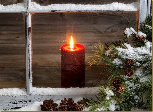 Christmas red candle with snow covered home window and pine trees