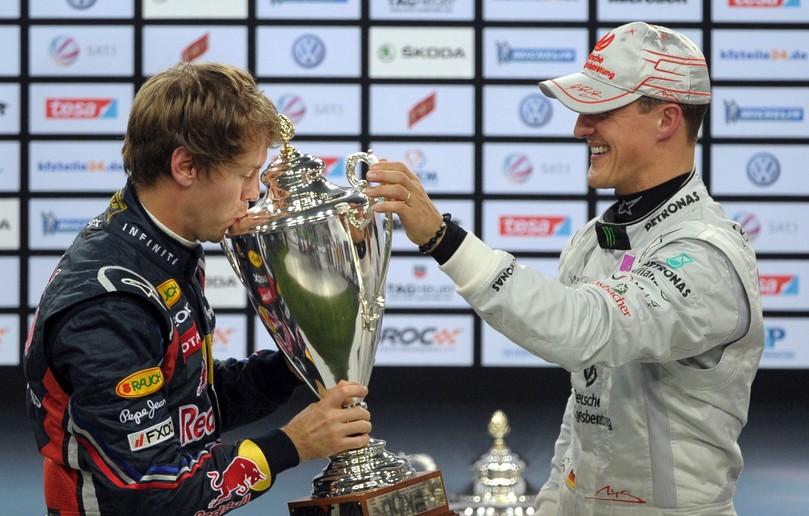 Себастьян Феттель целует победный трофей Гонки чемпионов 2011 из рук Михаэля Шумахера