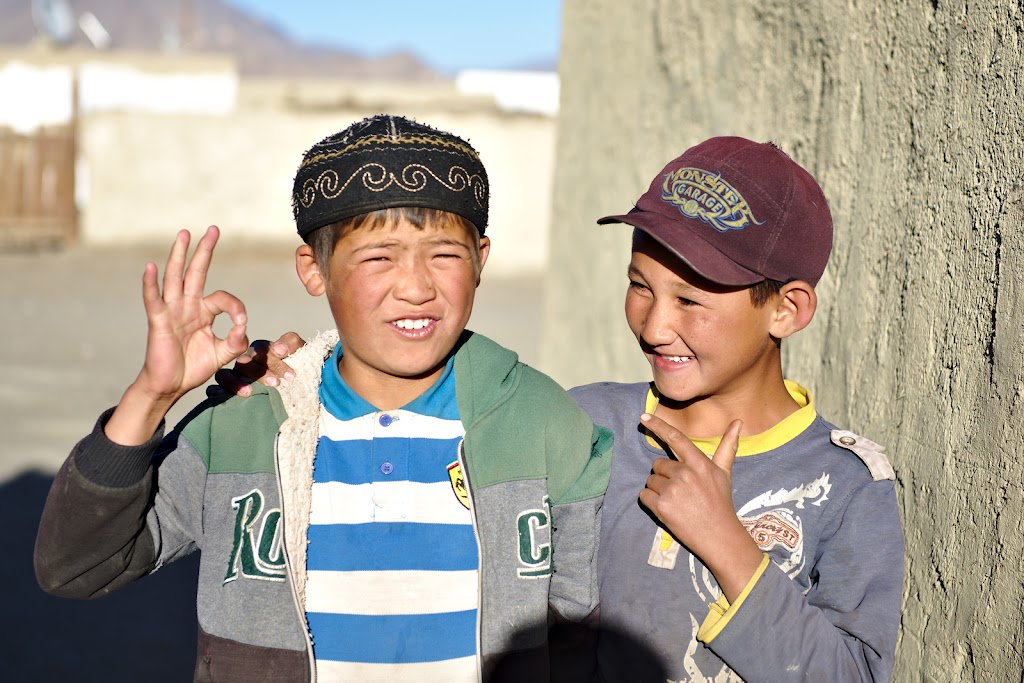 Kyrgyz boys helping out in finding one of the shops in Karakul. With no official shops some locals have a room where they keep supplies and where you can find some really basic food-stuff.