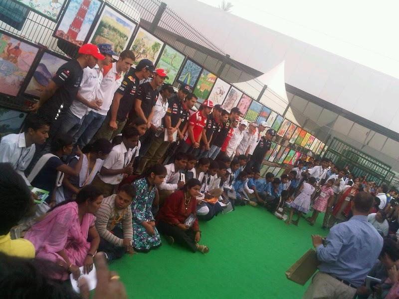 пилоты Формулы-1 с индийскими детьми на фоне рисунков на Гран-при Индии 2011