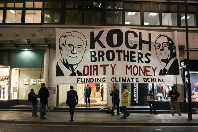 Outside the London office of Koch Industries, protesters gather under a large banner that reads, 'Koch Brothers Dirty Money Funding Cimate Denial'. Photo: P.Wolmuth / REPORT DIGITAL-REA / Re