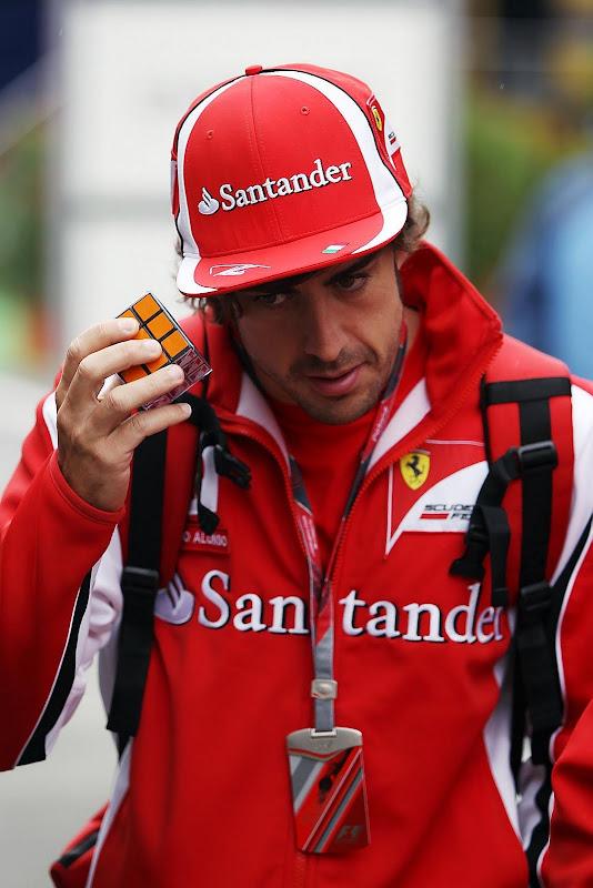 Фернандо Алонсо идет по паддоку с Кубиком Рубиком на Гран-при Венгрии 2011