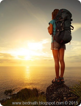 Tourist with backpack standing on a rock and looking to a sea; Shutterstock ID 121644487; PO: test; Job: dev; Client: drone