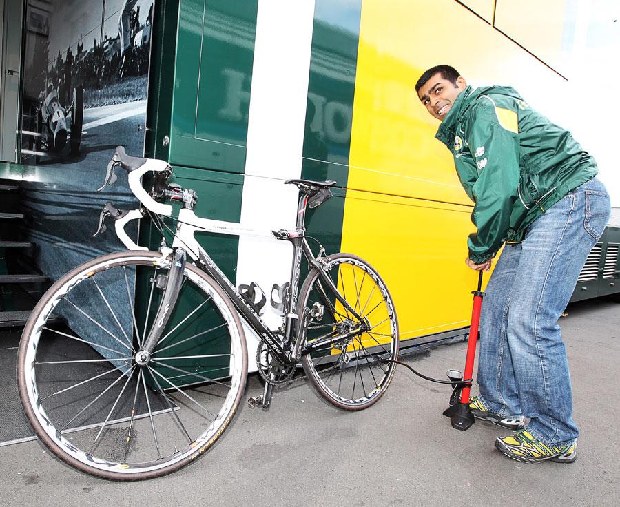 Карун Чандхок накачивает колесо велосипеда на Гран-при Германии 2011