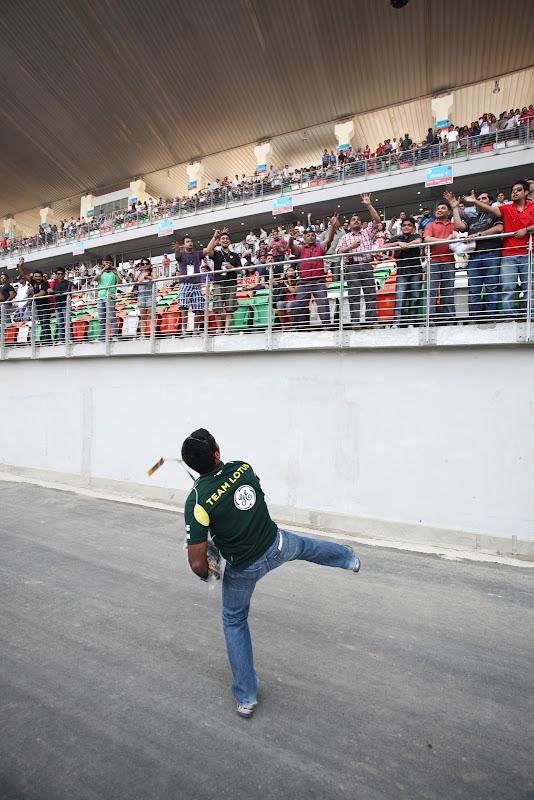 Карун Чандхок бросает кепки болельщикам на трибунах Гран-при Индии 2011