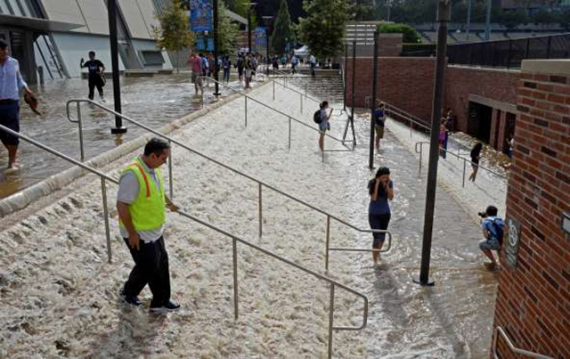 In this 29 July 2014 file photo, water cascades down a stairway leading to a parking structure across from Pauley Pavilion on the UCLA campus after a water main rupture under nearby Sunset Boulevard flooded a large area of the campus in the Westwood section of Los Angeles. The U.S. Environmental Protection Agency projects that it will cost $384 billion over 20 years to maintain the nation's existing drinking water systems, which will require tens of thousands of miles of replacement pipe and thousands of new or renovated plants. Photo: Mike Meadows / AP Photo
