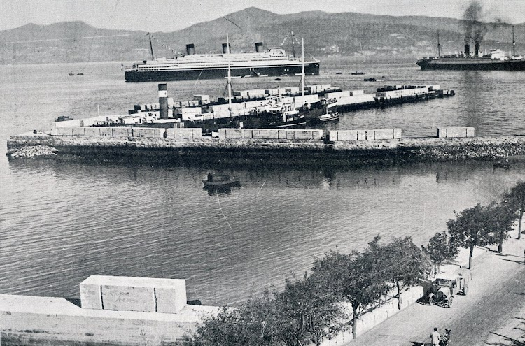 El pontón EBROS dando consumo a pesqueros en el puerto de Vigo. Al fondo, la característica silueta del desafortunado ATLANTIQUE. Foto de la Memoria del Puerto de Vigo. Año 1931.jpg