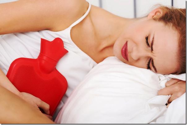 Beautiful caucasian woman lying with hot water bag