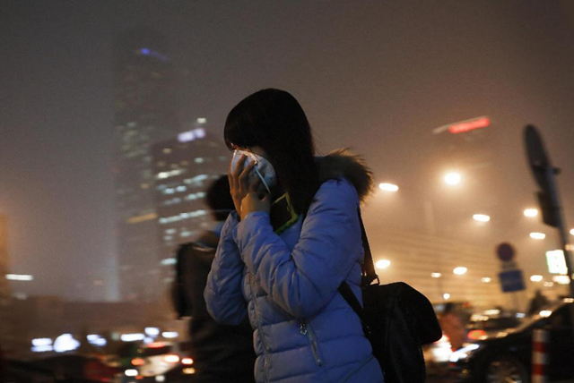 A woman covers her face with a mask as she rushes to a subway station on a heavily polluted day in Beijing Tuesday, 8 December 2015. Beijing's red alerts for smog are as much about duration as they are about severity of pollution forecasts. The forecasting model must predict three or more days of smog with levels of 300 or higher on the city's air quality index - which typically would include having levels of dangerous PM 2.5 particles of about 10 times the safe level. Photo: Andy Wong / AP Photo