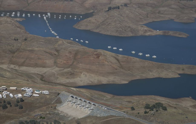 In this aerial photo taken Tuesday, 28 April 2015, a spillway sits more than a 100 yards away from the water level of New Hogan Lake near Valley Springs, east of Lodi, California. The State Water Resources Control Board is considering sweeping mandatory emergency regulations to protect water supplies as water levels at some of California's lakes and reservoirs continue to decline. Photo: Rich Pedroncelli / Associated Press