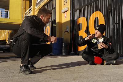 Кими Райкконен пьет кофе и разговаривает с механиком на тестах в Валенсии 24 января 2012