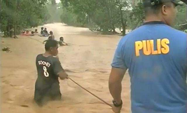 Rescuers help Filipinos through floodwaters caused by Typhoon Koppu, 19 October 2015. Photo: AFP