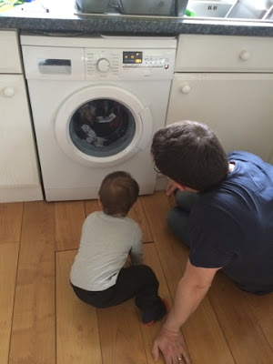 Baby boy and Daddy watching the washing machine