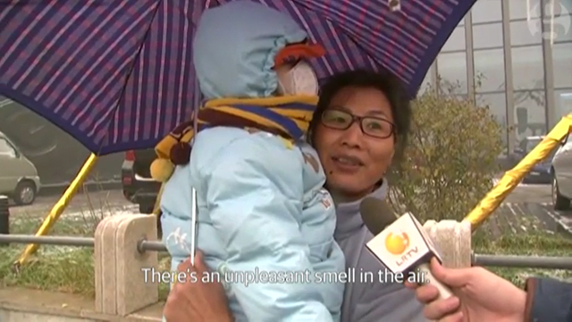 A woman in Shenyang, China, holds her child, who wears a mask against record pollution levels, 8 November 2015. She says, 'There is an unpleasant smell in the air.' Photo: LRTV / The Guardian