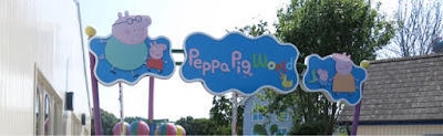 The sign you are greeted with as you enter Peppa Pig World. Including photo of Peppa and family.