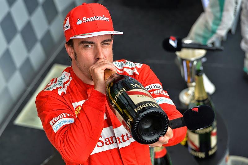 подмигивающий Фернандо Алонсо с шампанским на подиуме Гран-при Венгрии 2014