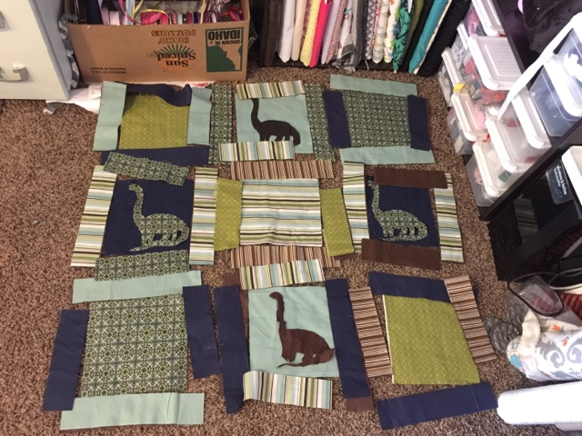 rag quilt laid out before being sewn with dinosaur appliques