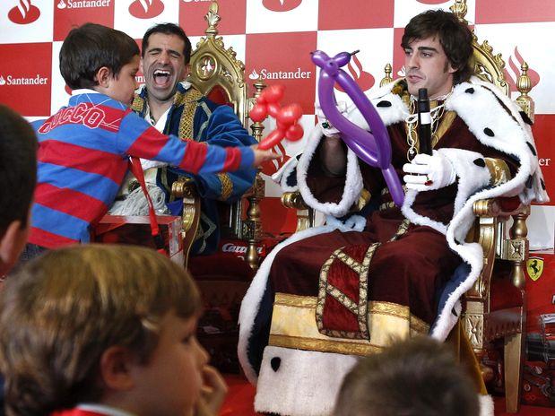 Фернандо Алонсо получает воздушные шарики от ребенка - Марк Жене смеется на рождественском мероприятии Santander 19 декабря 2011