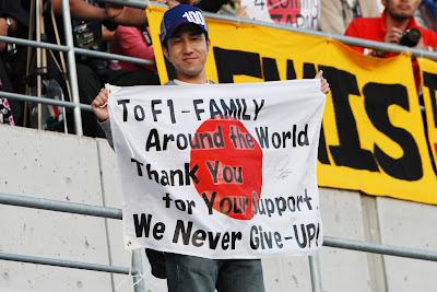 болельщик на трибунах Сузуки с японским флагом со словами благодарности на Гран-при Японии 2011
