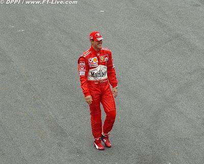 улыбающийся и ничего неподозревающий Михаэль Шумахер идет для общей фотографии в конце сезона на Гран-при Бразилии 2004