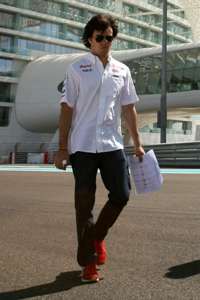Серхио Перес с забавным лицом идет по треку Яс Марины на Гран-при Абу-Даби 2011