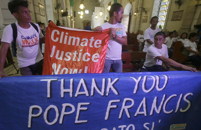 Environmental activists display a banner as they prepare to listen to speeches inside a Roman Catholic church in Manila, Philippines, on 18 June 205, to coincide with Pope Francis' encyclical on climate change. Photo: Bullit Marquez / AP