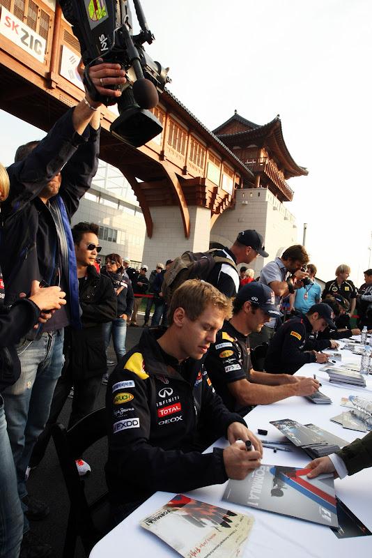 Себастьян Феттель во время автограф-сессии и телевизионная камера над его головой на Гран-при Кореи 2011