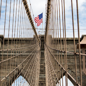 American Flag on the Brooklyn Bridge by Thomas Shaw - Buildings & Architecture Bridges & Suspended Structures ( bricks, sky, steel, cables, flag, city, clouds, new york, american flag, structure, fly, 2018, new york city, light, flag pole, architectural detail, brooklyn, nyc, bridge, brooklyn bridge, photography, architecture )