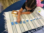 This 1st year student is working on multiples of five. We offer many different materials, both to explore operations (multiplication is adding the same number, several times) and to memorize math facts.