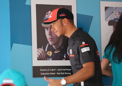 Льюис Хэмилтон на фоне плаката Себастьяна Феттеля на автограф-сессии Гран-при Абу-Даби 2011
