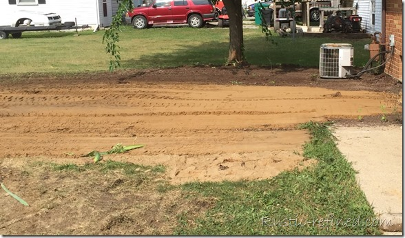using sand and a bobcat to fill in an old septic tank