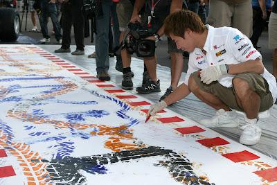 Камуи Кобаяши ставит автограф на картине Pirelli на Гран-при Италии 2011 в Монце