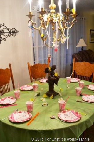 childrens fairy party table with pink settings on green cloth