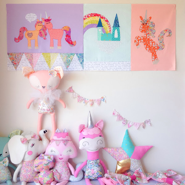 Liberty unicorn quilt blocks hanging above dolls