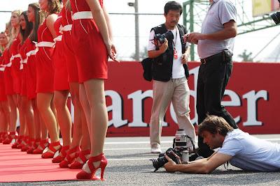фотограф лежит на асфальте позади пит-герлз на параде пилотов Монцы на Гран-при Италии 2011