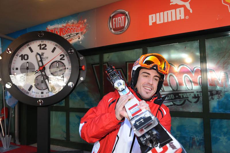 Фернандо Алонсо тащит горные лыжи на плече на фоне часов на Wrooom 2012