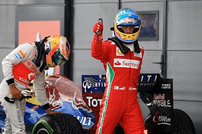 Льюис Хэмилтон трогает резину Pirelli на болиде Red Bull после квалификации на Гран-при Великобритании 2012