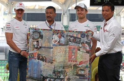Михаэль Шумахер и Нико Росберг держат плакат болельщиков на Гран-при Малайзии 2012