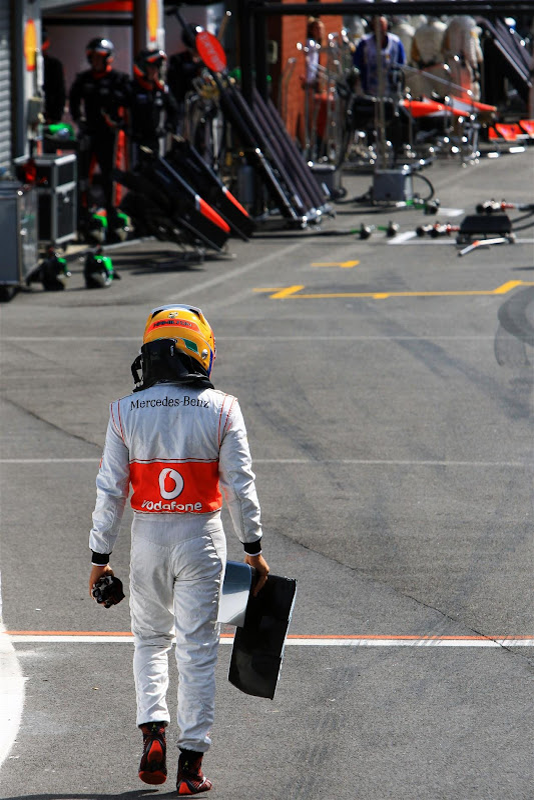 Льюис Хэмилтон несет обломок переднего крыла McLaren на Гран-при Бельгии 2012