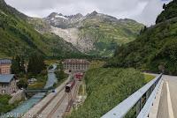 Das Örtchen Gletsch, eigentlich nur eine Häuseransammlung, die mit der Furka-Dampfeisenbahn entstanden ist. In der Bildmitte die Geröllwanne des Rhonegletscher und die noch sehr junge Rhone, die nach über 800 km in Südfrankreich in der Camargue ins Mittelmeer mündet.