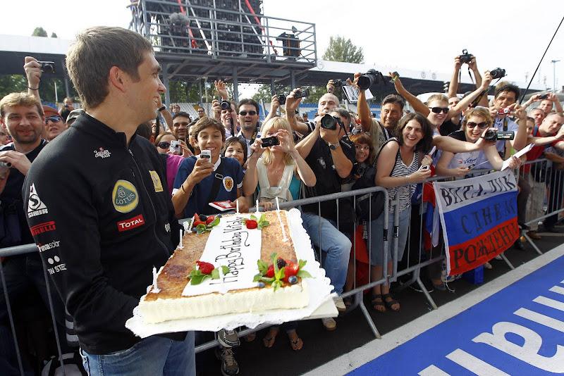 Виталий Петров с праздничным тортом на фоне болельщиков на Гран-при Италии 2011
