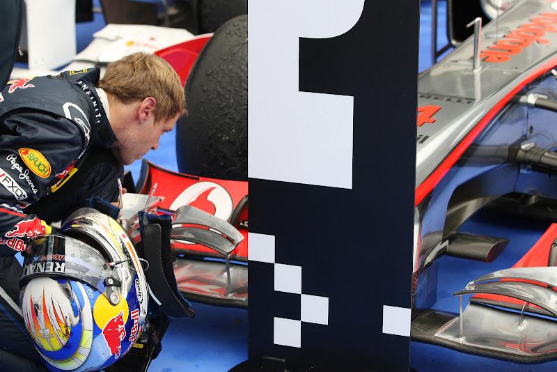 Себастьян Феттель осматривает переднее крыло McLaren после финиша гонки на Гран-при Венгрии 2011