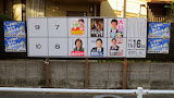 A campaign board, featuring the Fukuoka mayoral candidates. The small posters on either side are using the Fukuoka Hawks baseball team to encourage people to vote