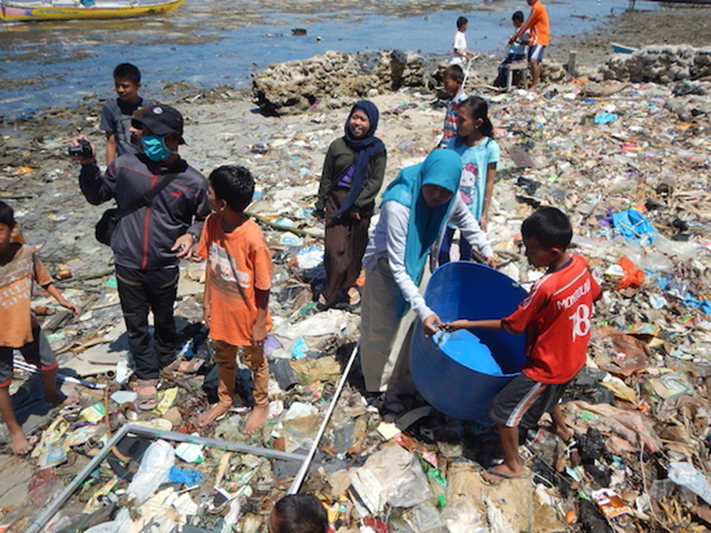 Students help pick up plastic from a beach in Indonesia, 8 August 2015. UC Davis researchers found plastic fragments and textile fibers in 25 percent of fish sold in Indonesian and California markets. Photo: Susan Williams / UC Davis