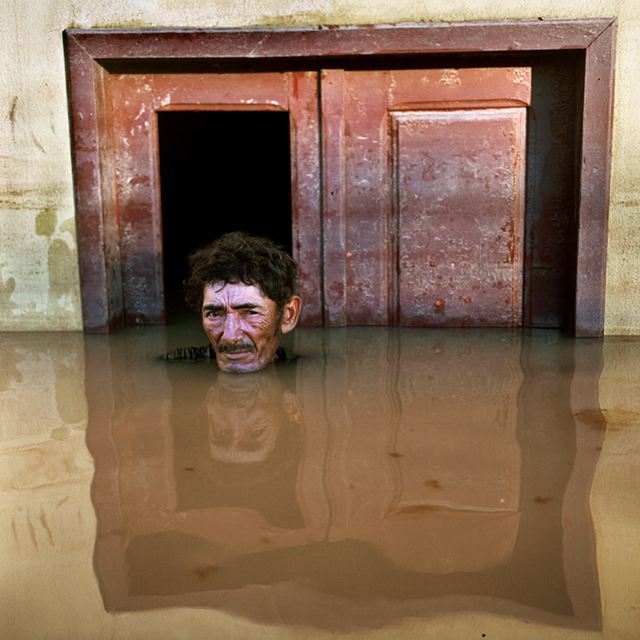 João Pereira de Araúj, of Rio Branco, Brazil, stands in floodwater up to his neck, 14 March 2015. 'I have seen many floods in my life, but never this high. My home is built on stilts, but now the lower floor is submerged. I look out of the window and see street after street under water – so many homes and shops. All we can do is wait for the water to go down, clean up and continue.' Photo: Gideon Mendel