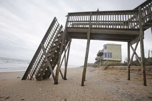 In this photo from 4 February 2015, beach access stairs are broken in front of a home at Vilano Beach. Homes built on strands of white sand in Vilano Beach now teeter precariously as high tidewaters cover their front steps. Photo: John Raoux / Associated Press