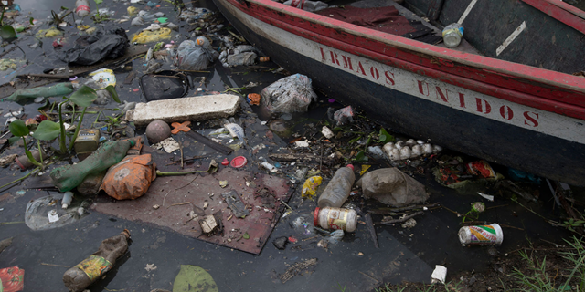 A boat surrounded by floating trash in the Meriti polluted river that flows into the Guanabara bay, in Rio de Janeiro, Brazil, on 5 November 2015. Photo: Silvia Izquierdo / AP Photo